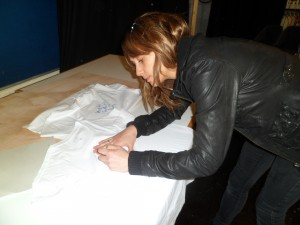 Samia Ghadie signing TLC T-Shirts to raise funds for Tomas